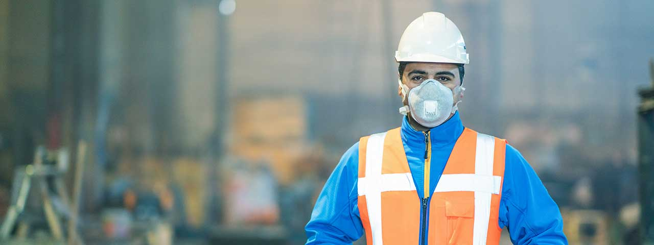 A construction worker wearing a respirator.