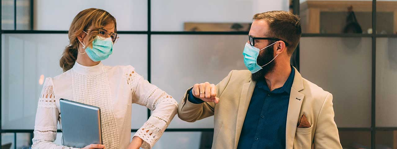 Two people wearing face masks bumping their elbows together.