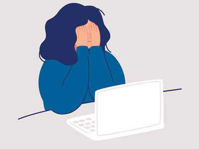 A person sitting in front of their laptop computer with anxiety.