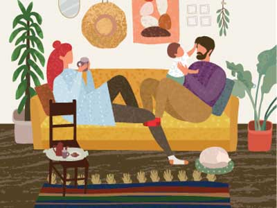 A mother and father sitting on a couch with a small child.